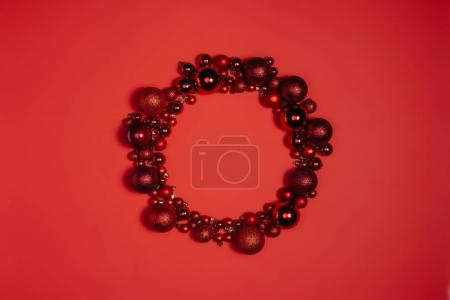 top view of decorative christmas toys arranged into wreath isolated on red
