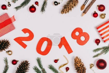 flat lay with arranged pine cones, wrapped gifts, christmas toys and 2018 year sign isolated on white