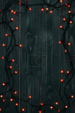 top view of christmas lights on dark wooden tabletop