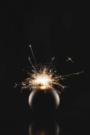 close up view of burning sparklers in christmas toy isolated on black