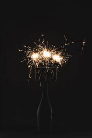 close up view of burning sparklers in bottle isolated on black