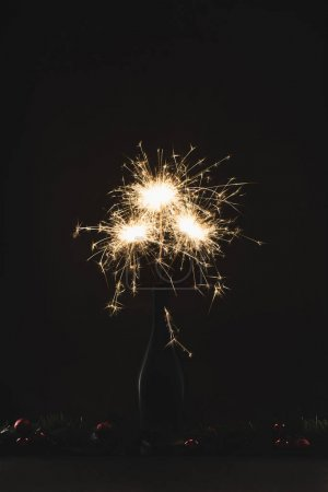close up view of burning sparklers in bottle and christmas balls isolated on black