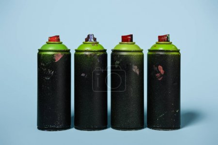 close up view of arranged cans with aerosol paint isolated on blue