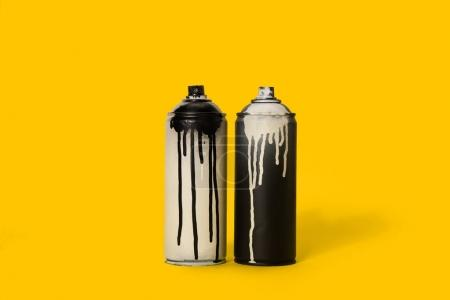 Photo for Close up view of black and white aerosol paint in cans isolated on yellow - Royalty Free Image