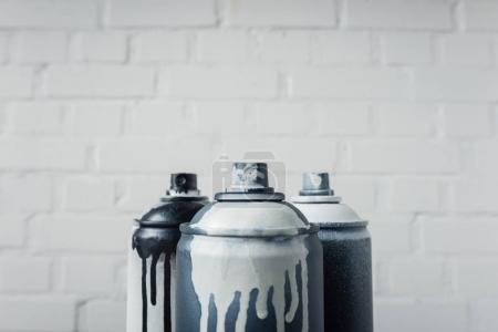 close up view of spray paint in cans with brick wall background