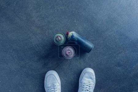 Photo pour Vue partielle de l'homme debout près de peinture en aérosol utilisée dans des bidons - image libre de droit