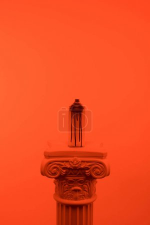orange toned picture of aerosol paint in can on column