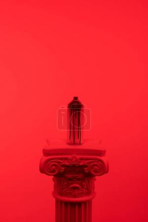 red toned picture of aerosol paint in can on column