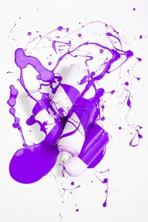 close up view of spray paint in cans covered with purple paint isolated on white