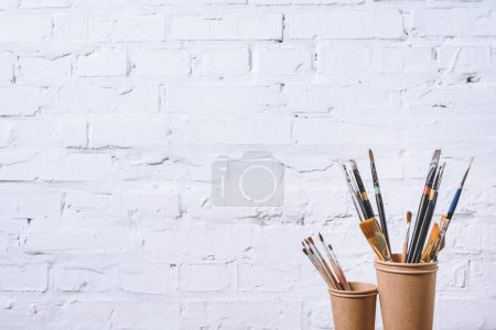 Photo for Paint brushes in paper cups on white wall - Royalty Free Image