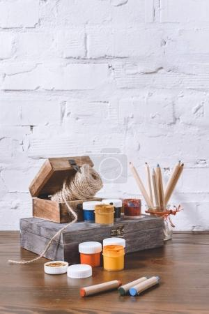 poster paints and wooden boxes on table