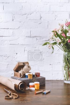 Photo pour Bouquet de fleurs et d'affiches peintures sur table en bois - image libre de droit