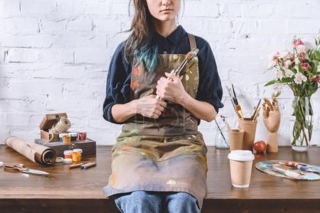 cropped image of female artist sitting on table and holding brushes in workshop
