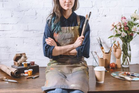 cropped image of female artist sitting on table with crossed arms and holding brushes