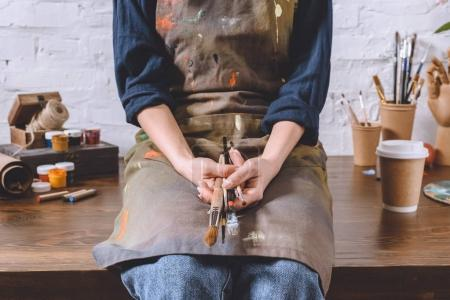 cropped image of female artist sitting on table and holding brushes