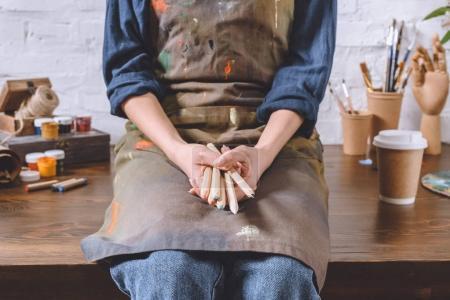 Photo pour Image recadrée de l'artiste féminine assis sur la table et la tenue des crayons - image libre de droit