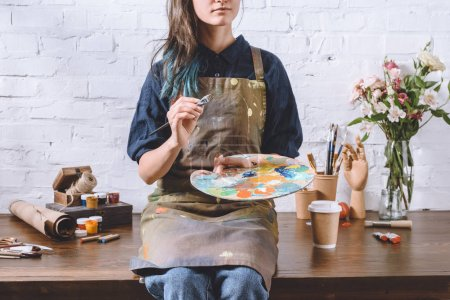 cropped image of artist holding palette and brush