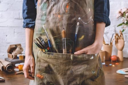 Photo for Cropped image of artist with brushes and hand in apron pocket - Royalty Free Image