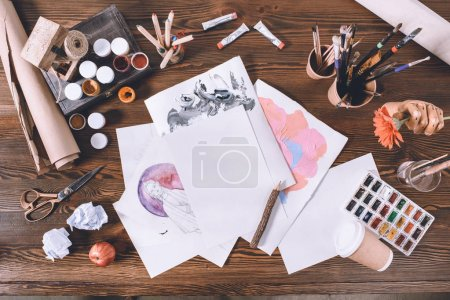 top view of designer workplace with sketches and paints