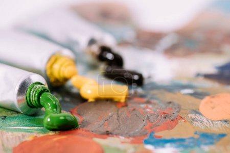 enfoque selectivo de la paleta con pinturas de colores en tubos