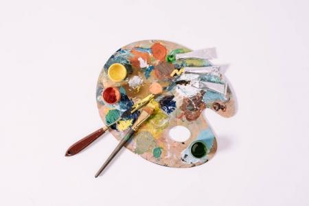 vista superior de la paleta con pinturas de colores aislados en gris
