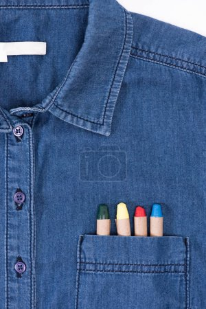 close-up view of stylish denim shirt with colorful pastels in pocket