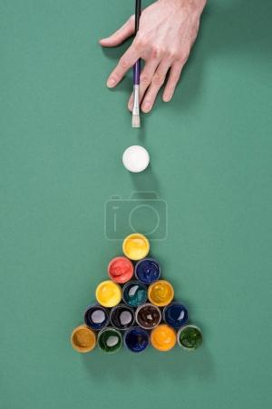 cropped shot of person playing billiard with paints