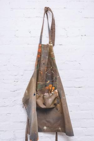 brown artist apron with paint brushes hanging on brick wall