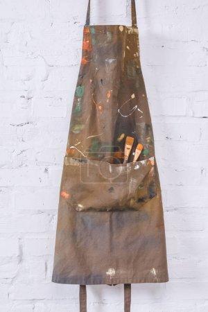 Photo pour Tablier marron avec pinceaux suspendus au mur de briques - image libre de droit
