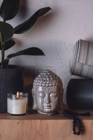 Photo for Sculpture of buddha head, burning candle and yoga mats on wooden shelf - Royalty Free Image