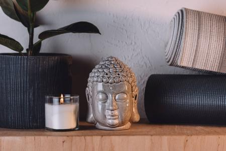 sculpture of buddha head, burning candle and yoga mats on wooden shelf