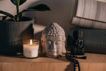sculptures of buddha and yoga mats on wooden shelf