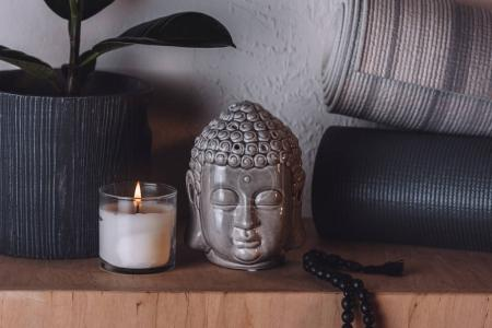 sculpture of buddha head and yoga mats on wooden shelf