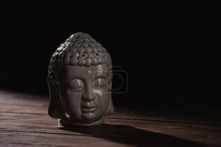 sculpture of buddha head on wooden table