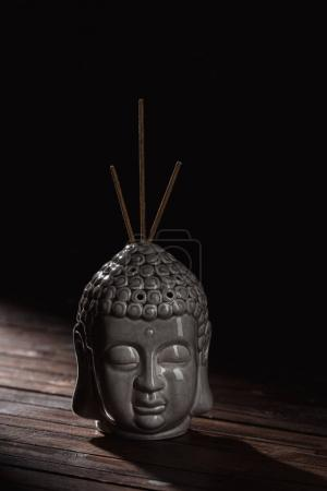 Photo for Sculpture of buddha head with incense sticks - Royalty Free Image