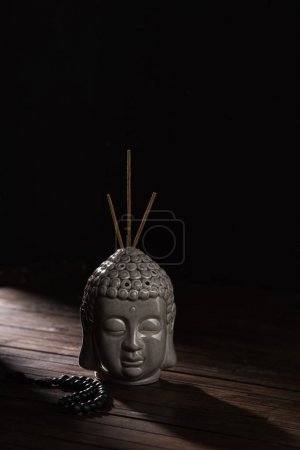 sculpture of buddha head with incense sticks on wooden table