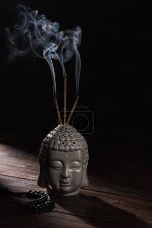 sculpture of buddha head with burning incense sticks