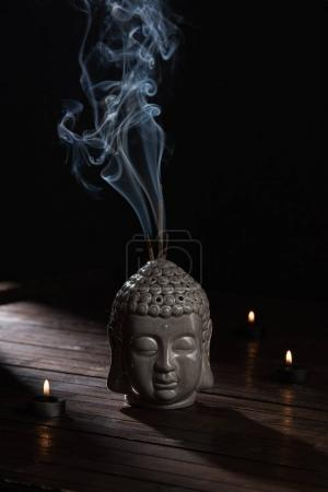 sculpture of buddha head with burning incense sticks and candles on table