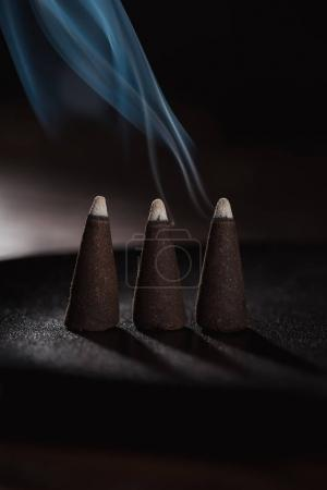 three burning incense sticks with blue smoke on black