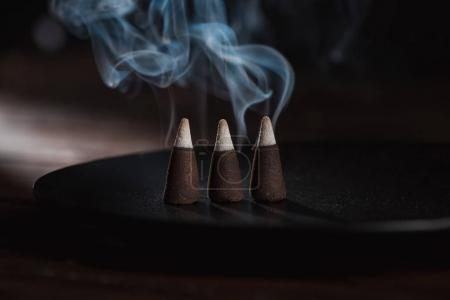 three burning incense sticks with blue smoke