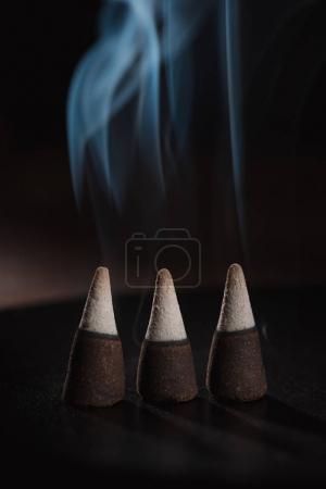 three burning incense sticks with smoke on dark surface