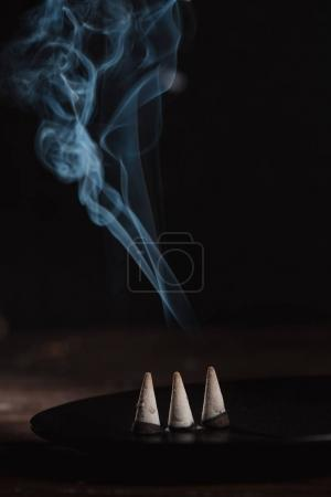 three burning incense sticks with smoke on table