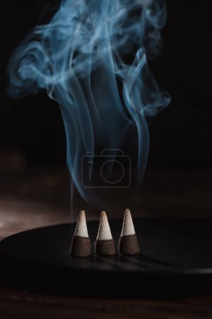 three burning incense sticks with smoke on black