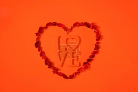top view of heart from dried fruits with word love isolated on orange