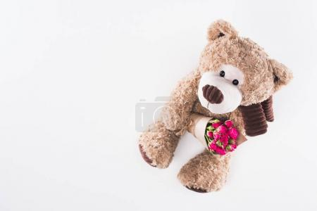 top view of teddy bear with bouquet of pink roses isolated on white