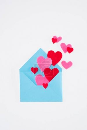 top view of blue envelope with colored hearts isolated on white, valentines day concept