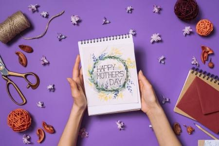 partial view of woman holding happy mothers day postcard in hands with decorations around isolated on purple