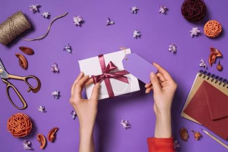 partial view of woman holding present with card isolated on purple