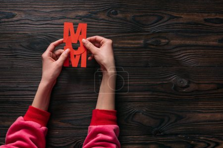 cropped shot of woman holding mom lettering in hands