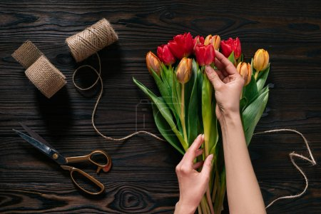 Photo for Partial view of female hands, rope, scissors and bouquet of flowers on wooden surface - Royalty Free Image